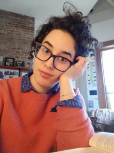Cihan (read Jehan), a 35-year old woman with curly dark brown hair, prominent eyebrows and light wheat colored skin sits at her desk, wearing a pink sweater and glasses and resting her head on her left hand. She looks like many other people with roots in lands bordering the Mediterranean sea.